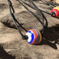 Rainbow inspired round lampwork bead on adjustable leather cord.