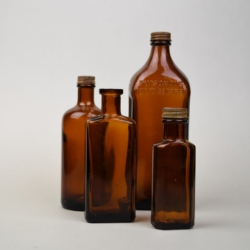 A COLLECTION OF BROWN GLASS BOTTLES