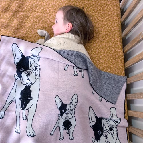 Girl wrapped under a Branberry Australian made knitted merino wool French bulldog (frenchie) blanket in Pale Pink