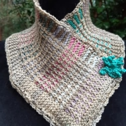 Small handknitted cowl in pastel shades finished with a lacy edging and trimmed with turquoise blue flowers