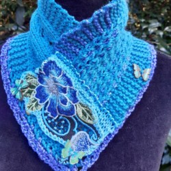small pure wool hand knitted cowl in shades of blue and featuring an embroidered piece
