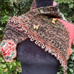 Handknitted small shawl in autumn tones featuring an embroidered flower piece and hand knitted flowers