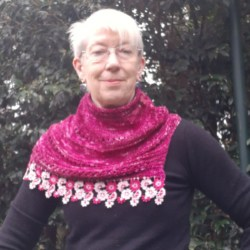 Handknitted wrap/cowl in hand dyed yarn in shades of pink with floral lace edging
