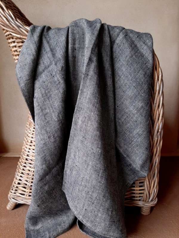 Image of a huckaback linen Bath Sheet in chevron black, hanging over a cane chair.