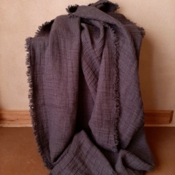Image of pure linen waffle throw blanket in grey with handcrafted edged fringe.