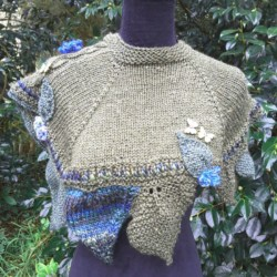 Handknitted wrap/ cape trimmed with leaves and flowers